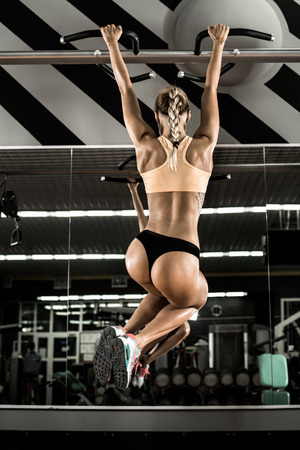 young fitness woman execute exercise on prelum abdominale, on horizontal bar in gym, vertical photo