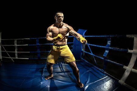 Photo pour Thai boxer on boxing ring, black bacground, horizontal photo - image libre de droit