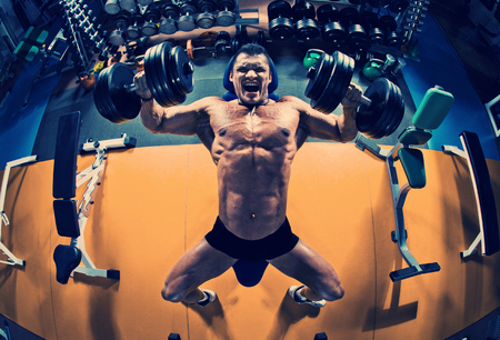 guy bodybuilder execute exercise press of dumbbells on pectoral muscle, in gym