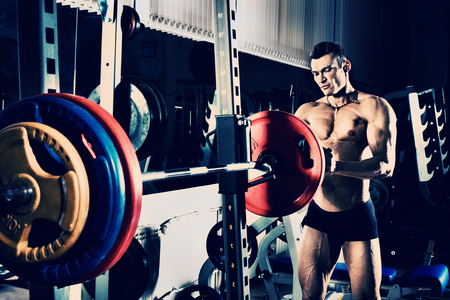 bodybuilder guy , execute exercise with weight, in gym, blue; violet tone