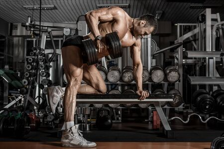 Photo for guy bodybuilder perform exercise with dumbbell, trained in dark gym - Royalty Free Image