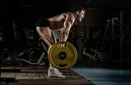 Foto per guy bodybuilder perform exercise deadlift with barbell, trained in dark gym - Immagine Royalty Free