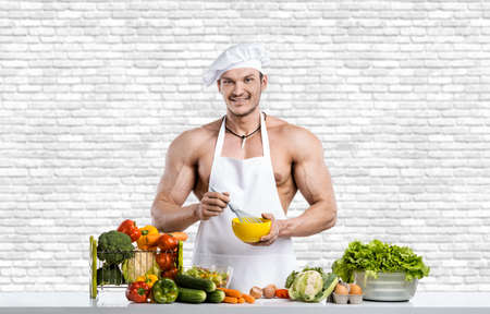 Photo pour Man bodybuilder in white toque blanche and cook protective apron, concoction vegetables, on white brick wall background. Healthy eating concept - image libre de droit