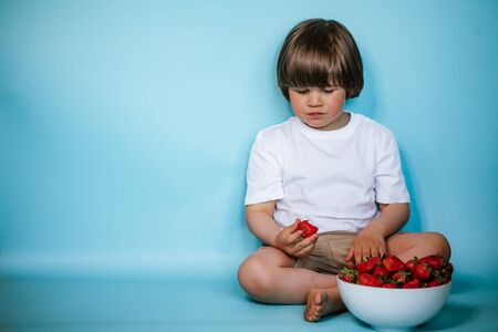 Photo pour Toddler boy sitting with bowl of strawberries on the blue background - image libre de droit