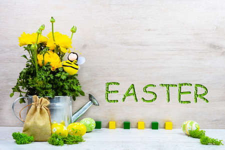 Foto de Yellow ranunculus buttercups in a metal watering can, decorative bee, Easter painted eggs, a canvas bag of gifts on a wooden background with the inscription Easter. Sample, mockup of Easter card - Imagen libre de derechos