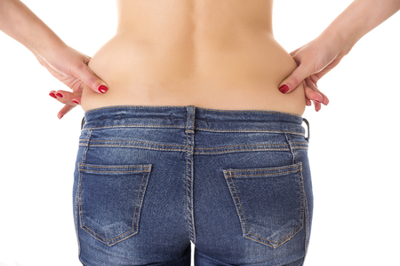 Foto de Woman hands compresses the the fat on the waist on a white background. - Imagen libre de derechos