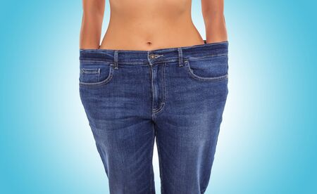 Photo pour Slender girl in big jeans on a blue background. Losing weight. - image libre de droit