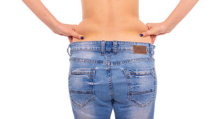 Photo for Slender girl in big jeans on a white background. Losing weight. - Royalty Free Image