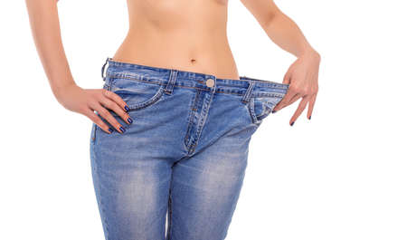 Photo pour Slender girl in big jeans on a white background. Losing weight. - image libre de droit