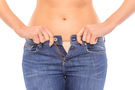 Photo pour Losing weight. Slender girl in big jeans on a white background. - image libre de droit