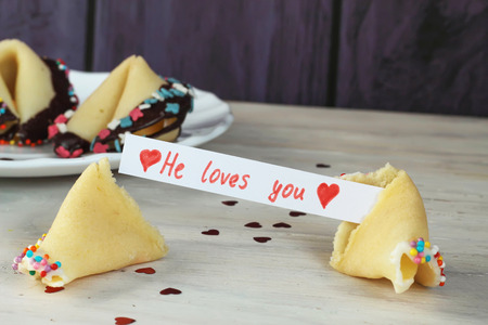 decorated open fortune cookie with blank he loves you valentines day