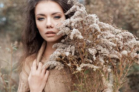 beautiful sad cute attractive woman in a beige sweater wide in a field of dry grass in autumn cold overcast day, photo of beige brown tones, chocolate hues
