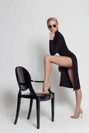 Foto de tall beautiful blonde girl in a black elegant dress in sunglasses on a black chair in the studio on a white background - Imagen libre de derechos