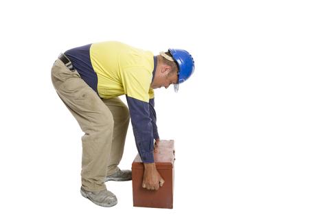 Photo pour A man using a poor lifting technique to move his tool box. Safety concept. - image libre de droit