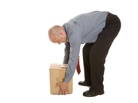 Photo pour A man using a poor lifting technique to move a box. Safety concept. - image libre de droit