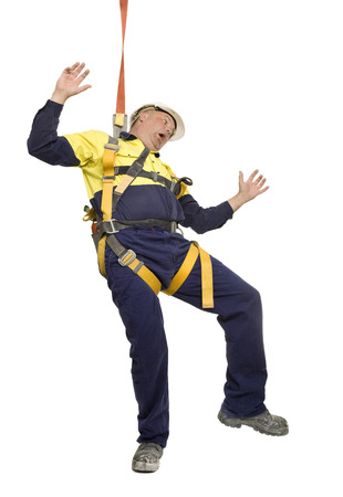 Foto de A worker falling over and wearing safety harness. - Imagen libre de derechos