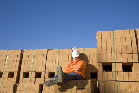 A worker sleeping on a pile of bricks.
