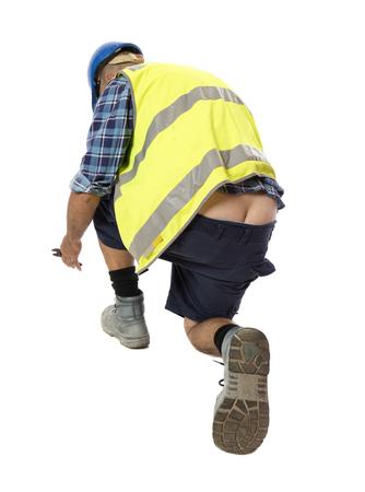 Foto de A worker crouching down to work, revealing more than intended. - Imagen libre de derechos
