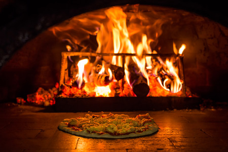 Photo pour Cooking pizza in a brick oven with woodfire - image libre de droit