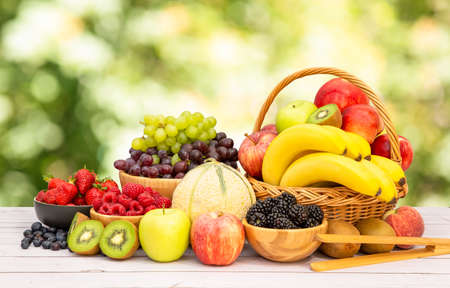 Photo for Group Healthy fresh fruit in a wooden basket, With vitamins c from bananas, kiwi, grapes, raspberries, blueberries, and blackberries, good for the body and diet food on the table in nature background. - Royalty Free Image