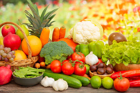 Photo for Group vegetables and Fruits Apples, grapes, oranges, pineapples, bananas in a wooden basket with carrots, tomatoes, guava, chili, eggplant, golden pod, green salad on wooden table in nature background - Royalty Free Image