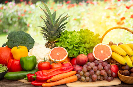 Photo for Group vegetables and Fruits Apples, grapes, oranges, and bananas in the wooden basket with carrots, tomatoes, guava, chili, eggplant, and salad on the table.Healthy food concept - Royalty Free Image