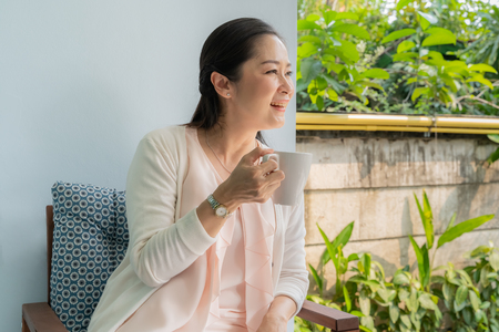 Photo for Middle-aged Asian women sit and sip coffee in the backyard. - Royalty Free Image