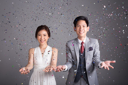 Photo pour Couple throw glittering paper to celebrate their wedding - image libre de droit
