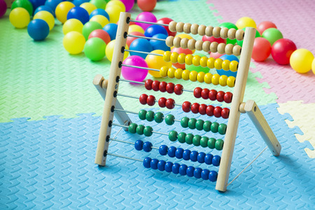 Photo pour Kids colorful abacus in playing room with plastic balls and soft foam ground - image libre de droit