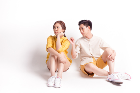 Foto de Young sulky asian female and young man trying to reconcile. sitting on white background - Imagen libre de derechos