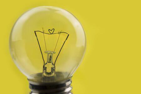 Photo pour close up old obsolete light bulb with heart shaped coil - image libre de droit