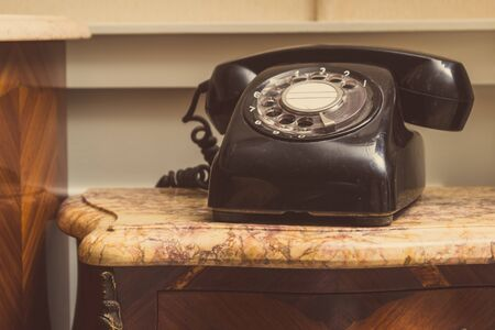 Foto per Old black telephone on stool - Immagine Royalty Free