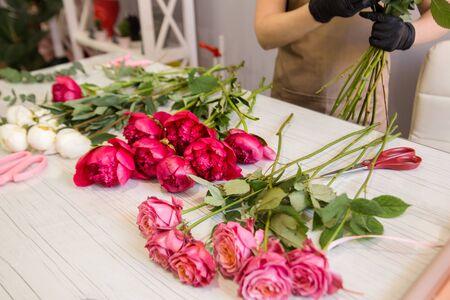 Photo pour red peonies lie on the table in the flower shop - image libre de droit