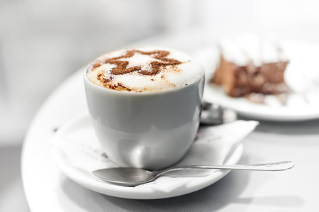Cup of coffee and cake in cafe, shallow DOF, high key.