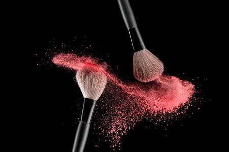 Photo pour Make-up brush with pink powder explosion on black background - image libre de droit