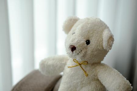 Photo pour white teddy bear doll toy sit on a sofa couch - image libre de droit