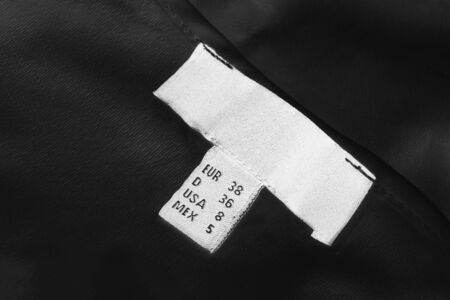 White size label on black cloth as a background