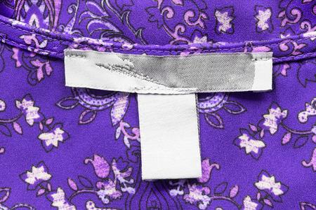 Blank clothes label on purple ornamental silk