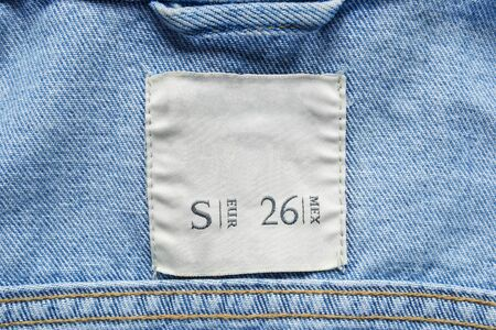 Size label on blue denim cloth as a background