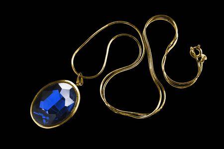 Photo pour Large blue sapphire pendant on gold chain isolated over black - image libre de droit
