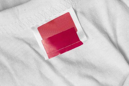 Photo pour Blank red clothes label on white cotton background - image libre de droit