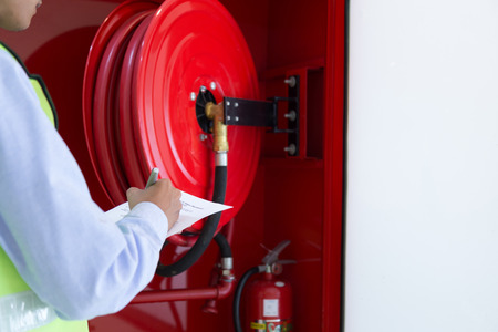Photo for Engineer inspection Fire extinguisher and fire hose. - Royalty Free Image