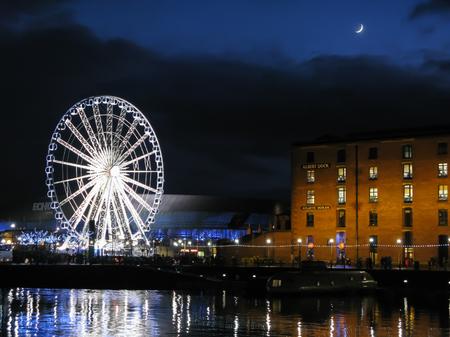 LIVERPOOL, ENGLAND - DECEMBER 15, 2012: Moon shining over Albert Dock warehouses and wheel at night