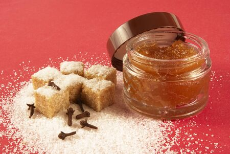 Body scrub with brown sugar crystals, spicinesses, on a red background