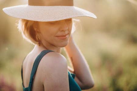 Photo pour Close-up portrait of a beautiful blonde girl in a hat at dawn. Soft selective focus. - image libre de droit