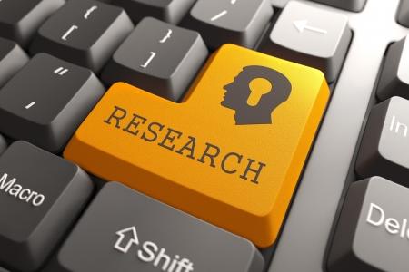 Foto de Orange Research Button on Computer Keyboard  Searching Concept  - Imagen libre de derechos