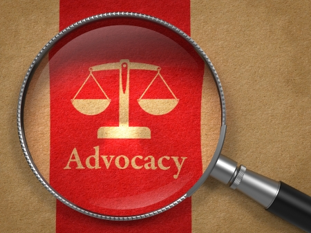 Advocacy Concept  Magnifying Glass with Word Advocacy and Icon of Scales in Balance on Old Paper with Red Vertical Line Background