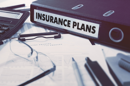 Foto de Insurance Plans - Ring Binder on Office Desktop with Office Supplies. Business Concept on Blurred Background. Toned Illustration. - Imagen libre de derechos