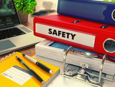 Photo pour Red Office Folder with Inscription Safety on Office Desktop with Office Supplies and Modern Laptop. Business Concept on Blurred Background. Toned Image. - image libre de droit