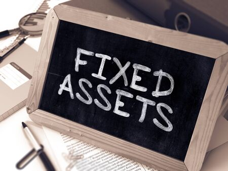 Fixed Assets Handwritten on Chalkboard. Composition with Small Chalkboard on Background of Working Table with Ring Binders, Office Supplies, Reports. Blurred Background. Toned Image.